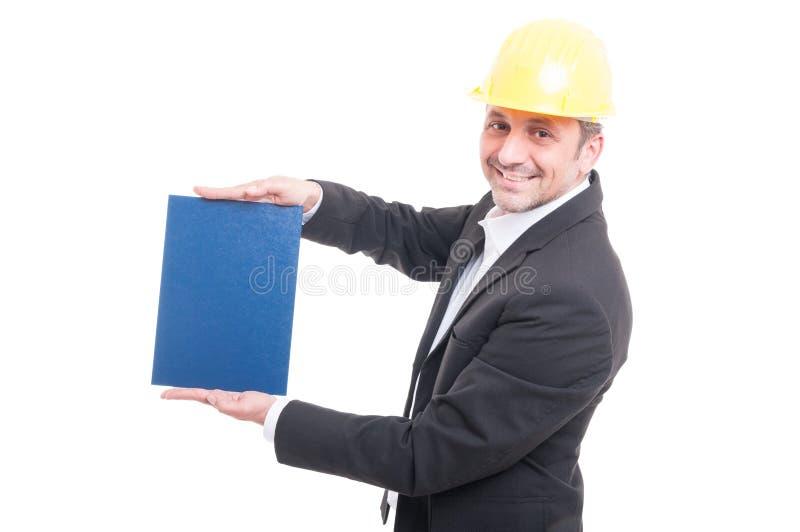 Retrato del casco de protección que lleva del contratista que sostiene la cartulina azul fotos de archivo libres de regalías