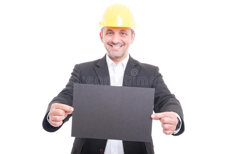Retrato del casco de protección que lleva del contratista que sostiene la cartulina gris fotos de archivo