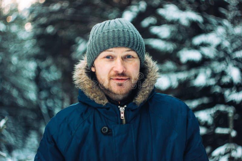 Retrato del cazador barbudo sonriente del silvicultor del viajero del hombre en bosque del invierno imagenes de archivo