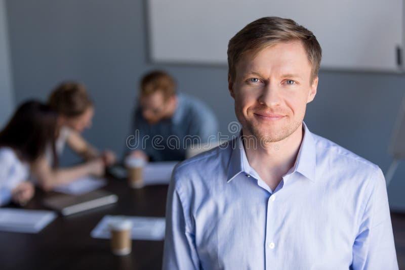 Retrato del CEO acertado sonriente de la compañía con el equipo en el backgrou imagen de archivo
