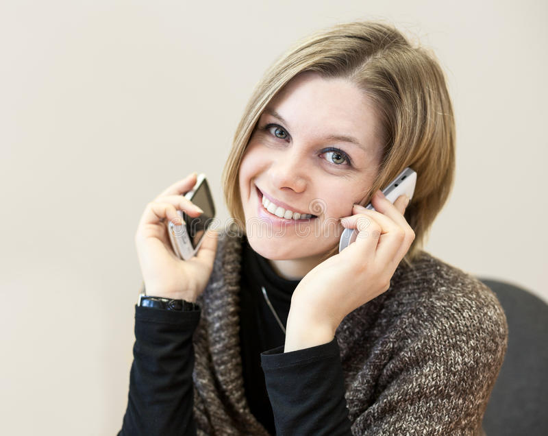 Retrato del cierre hermoso sonriente de la mujer joven para arriba con dos teléfonos móviles fotografía de archivo