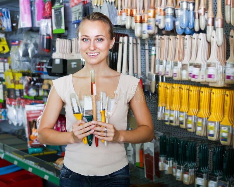 Retrato del cliente femenino joven que elige el cepillo imagen de archivo libre de regalías