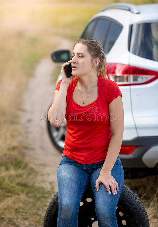 Retrato del coche roto siguiente que se sienta del conductor femenino en el campo y t fotografía de archivo