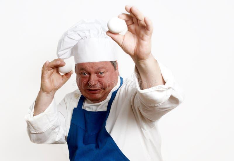 Retrato del cocinero con los huevos imagenes de archivo