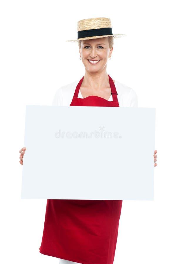 Retrato del cocinero de sexo femenino en sombrero con la tarjeta en blanco del anuncio imagen de archivo libre de regalías
