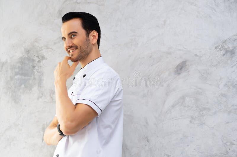 Retrato del cocinero hermoso sonriente que presenta contra con la barba que mira para echar a un lado imagen de archivo libre de regalías
