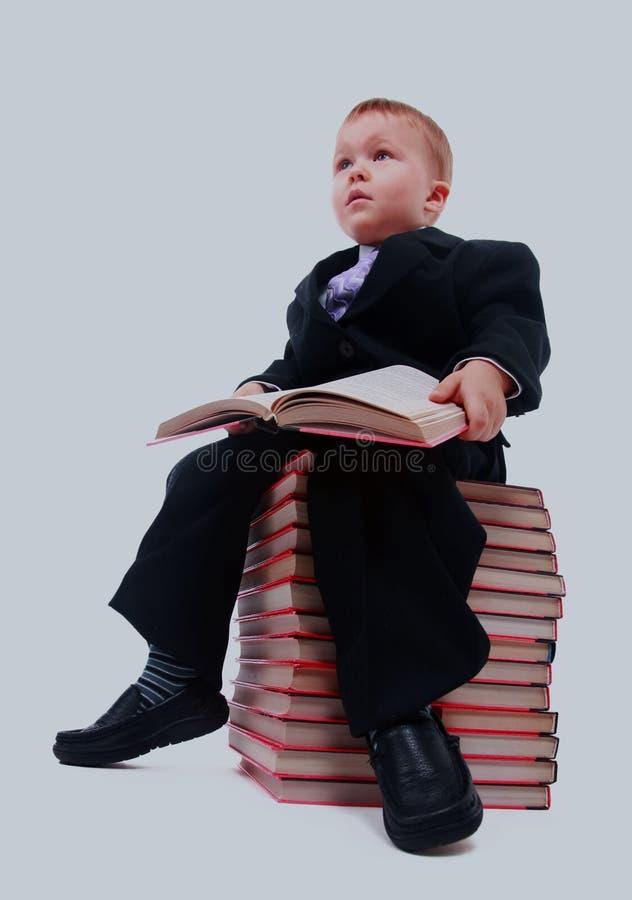 Retrato del colegial asiático que sostiene un libro y que se sienta en una pila de libros aislados en blanco imagen de archivo