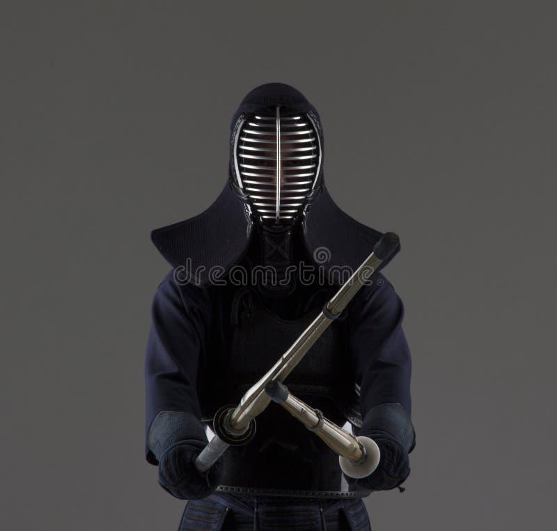 Retrato del combatiente del kendo del hombre con dos espadas de bambú en uniforme tradicional imagenes de archivo