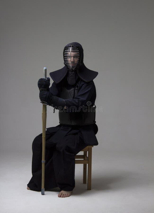 Retrato del combatiente del kendo del hombre con la espada de bambú en uniforme tradicional fotos de archivo