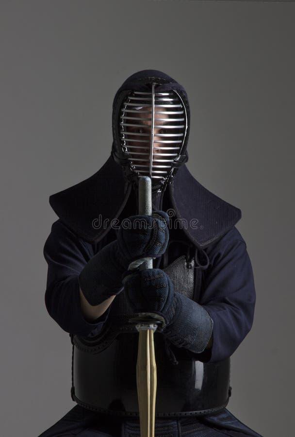 Retrato del combatiente del kendo del hombre con shinai en uniforme tradicional imagen de archivo