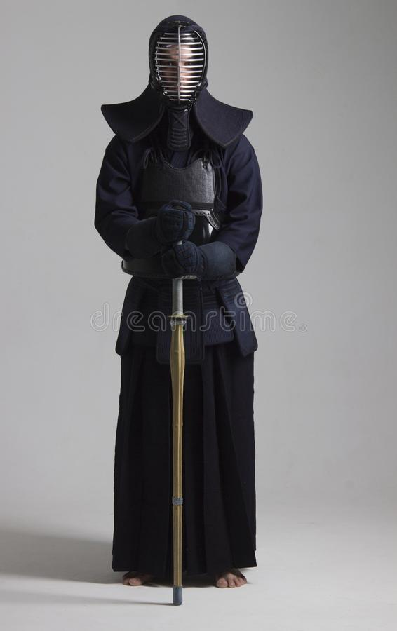 Retrato del combatiente del kendo del hombre con shinai Tirado en estudio foto de archivo