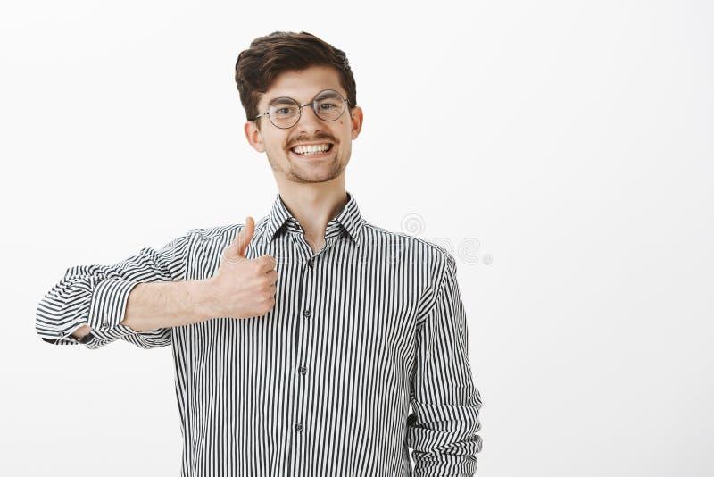 Retrato del compañero de trabajo amistoso activo y positivo en vidrios redondos, sonriendo alegre mientras que muestra los pulgar imagenes de archivo