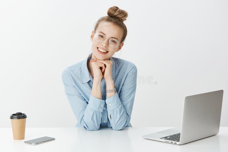 Retrato del compañero de trabajo femenino europeo feliz enfocado en vidrios, cabeza que se inclina en las manos y la mirada con s fotos de archivo