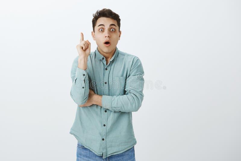 Retrato del compañero de trabajo masculino elegante atractivo sobre-emotivo en equipo de moda, aumentando el dedo índice en el ge imágenes de archivo libres de regalías