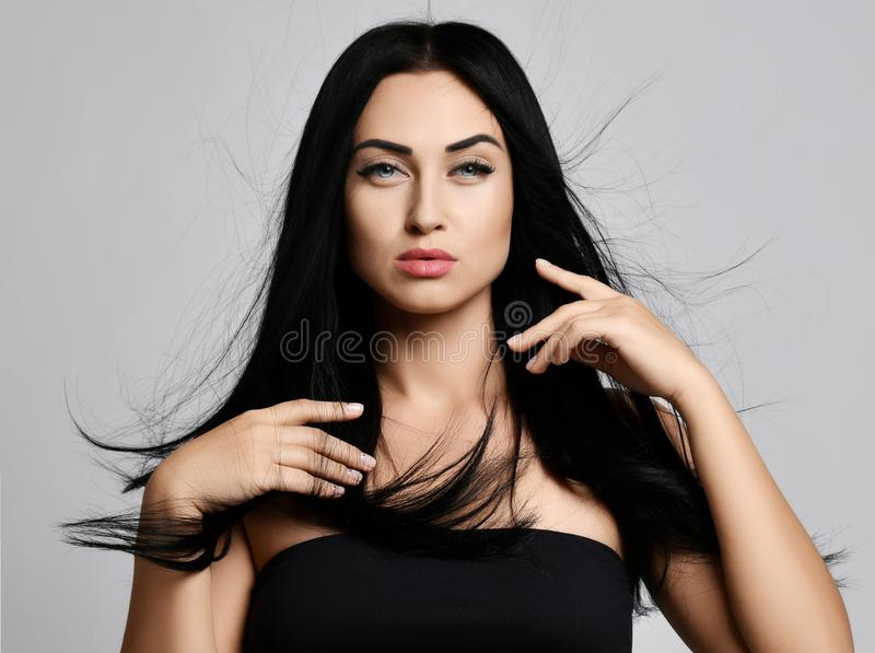 Retrato del concepto del anuncio de la morenita de la mujer que cepilla delicado su pelo perfecto que agita en el viento con sus  foto de archivo