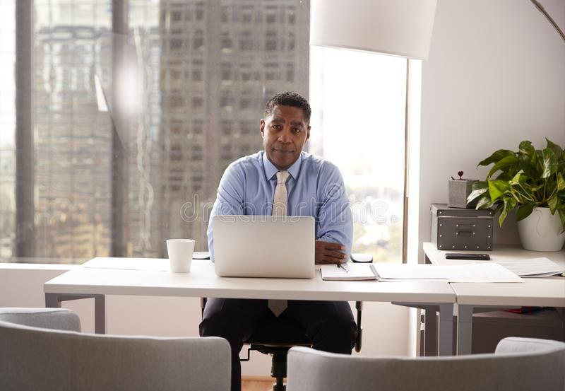 Retrato del consejero financiero de sexo masculino en la oficina moderna que se sienta en el funcionamiento del escritorio en el  fotos de archivo libres de regalías