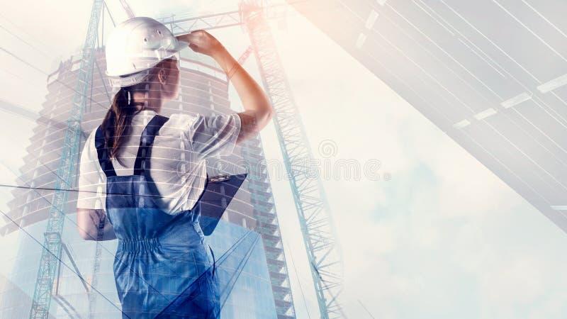 Retrato del constructor en un casco en fondo de la ciudad imagen de archivo libre de regalías