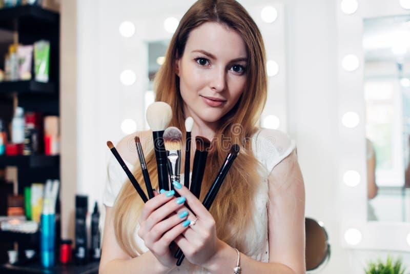 Retrato del cosmetólogo femenino que sostiene un sistema de cepillos del maquillaje en salón de belleza imagenes de archivo
