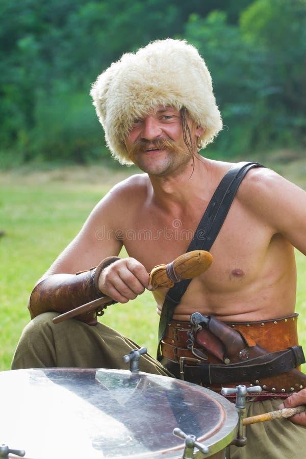 Retrato del cossack de Zaporozhian Sich, characternik del kozak que se sienta en un timbal, celebrando los palillos del tambor y  fotografía de archivo