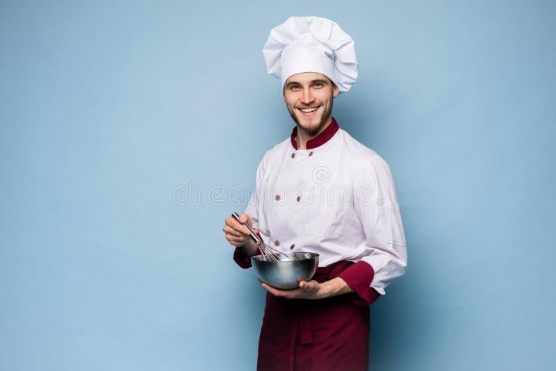 Retrato del cuenco de la tenencia del cocinero y del batidor sonrientes del alambre en fondo azul Cocinero que hace la comida imagen de archivo libre de regalías