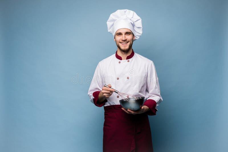 Retrato del cuenco de la tenencia del cocinero y del batidor sonrientes del alambre en fondo azul Cocinero que hace la comida fotografía de archivo libre de regalías