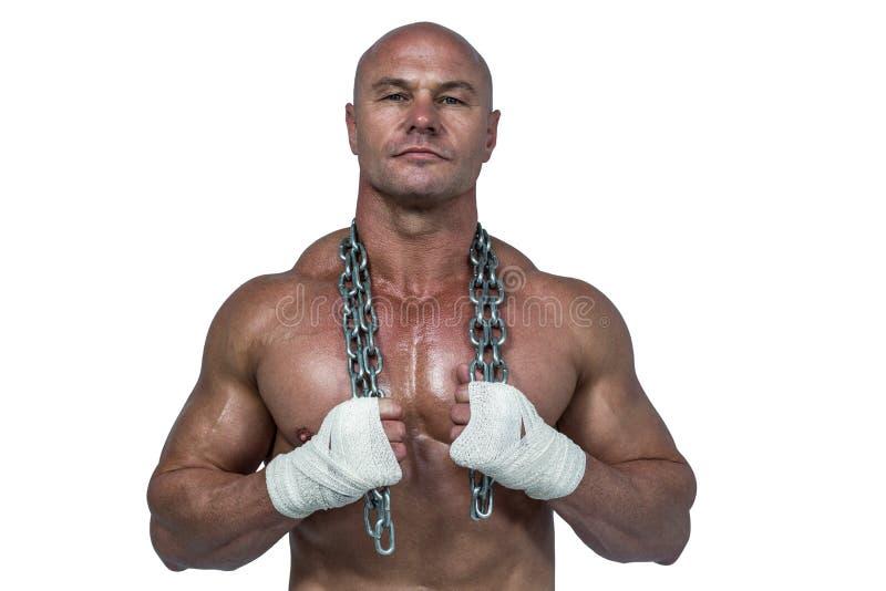 Retrato del culturista confiado que se sostiene de cadena alrededor de cuello foto de archivo libre de regalías