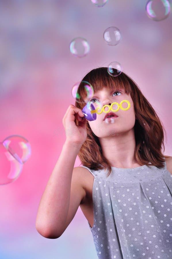 Retrato del día de fiesta de las burbujas de jabón del niño que soplan feliz imagenes de archivo