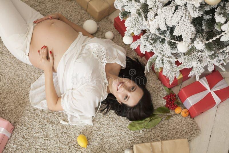 Retrato del día de fiesta hermoso del regalo del árbol del Año Nuevo de la Navidad de la mujer embarazada imagen de archivo libre de regalías