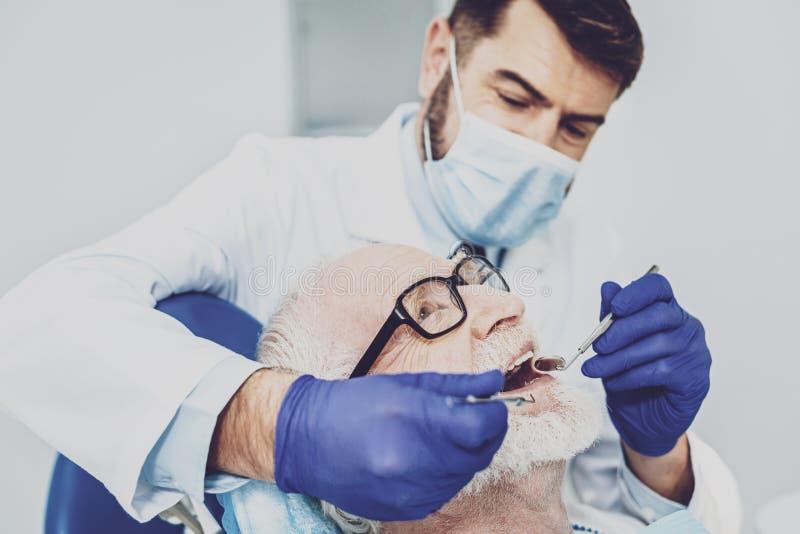 Retrato del dentista competente ese visitante de examen imagen de archivo