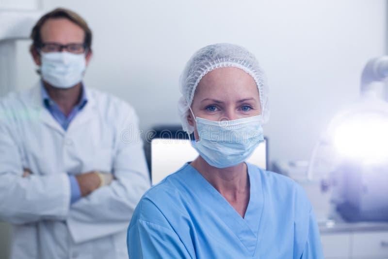Retrato del dentista y del ayudante de dentista que llevan la máscara quirúrgica imagen de archivo