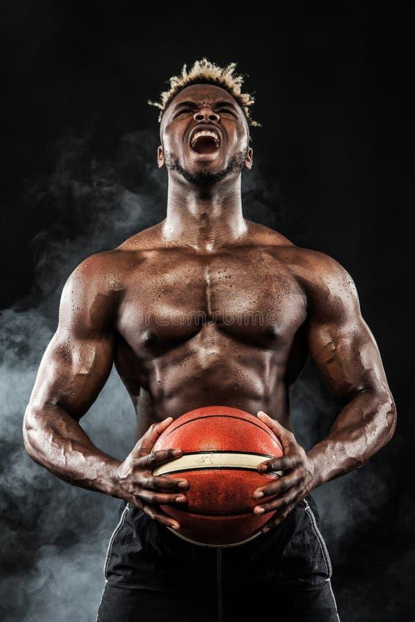 Retrato del deportista afroamericano, jugador de básquet con una bola sobre fondo negro Hombre joven apto en ropa de deportes fotos de archivo libres de regalías