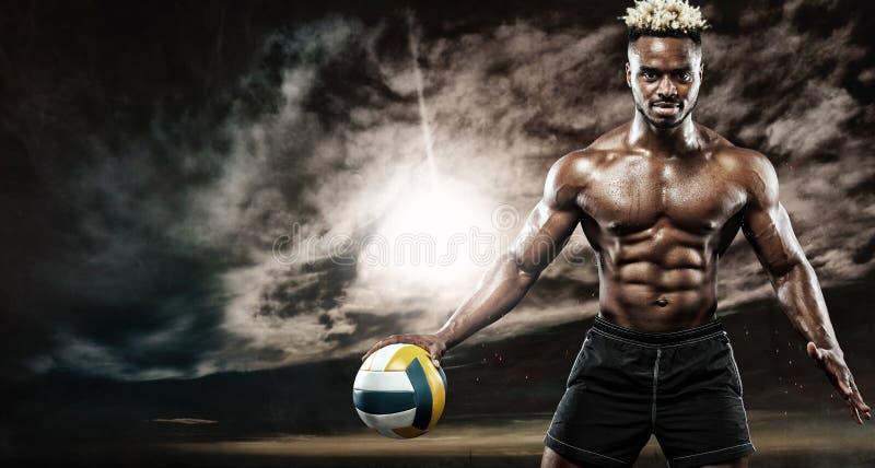 Retrato del deportista afroamericano, jugador de voleibol de playa con una bola sobre puesta del sol Hombre joven apto en ropa de fotografía de archivo libre de regalías