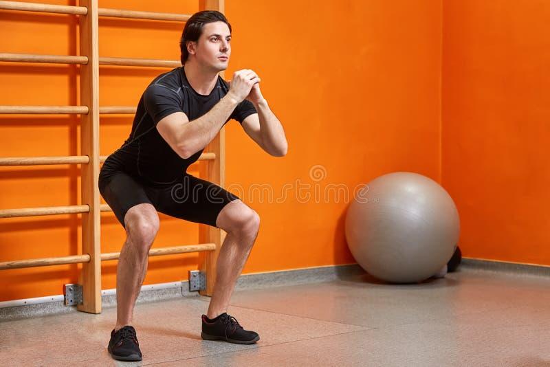 Retrato del deportista joven en el sportwear negro mientras que hace posición en cuclillas contra la pared anaranjada brillante e fotografía de archivo