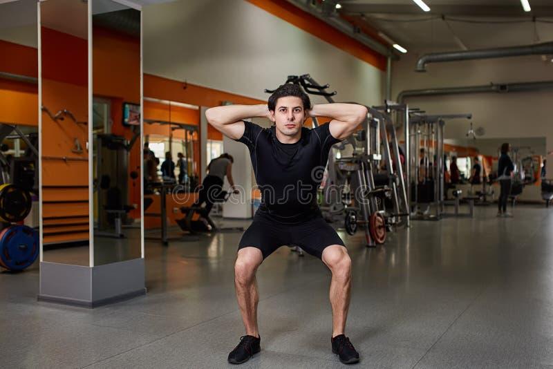 Retrato del deportista joven en el sportwear negro mientras que hace posición en cuclillas en gimnasio fotografía de archivo libre de regalías