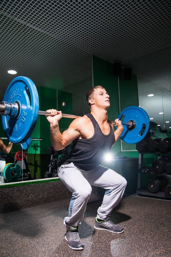 Retrato del deportista joven que hace posiciones en cuclillas en gimnasio con los pesos foto de archivo