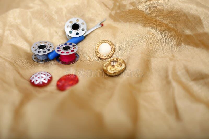 Retrato del destripador, del botón y de la bobina de la aguja en el paño de oro imagen de archivo libre de regalías