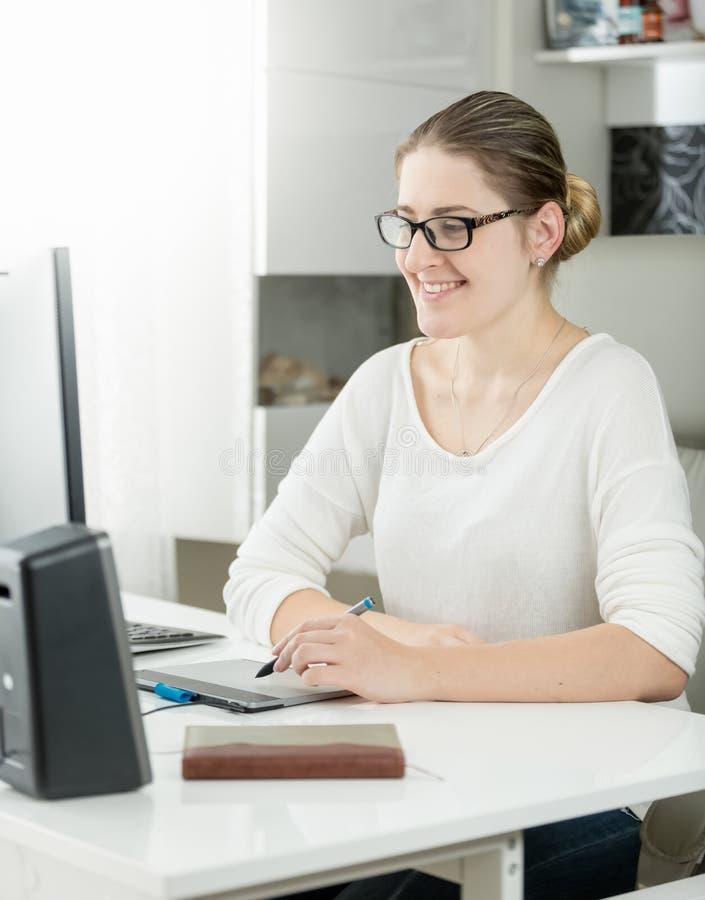 Retrato del diseñador gráfico de sexo femenino joven sonriente que trabaja en la oficina moderna fotos de archivo