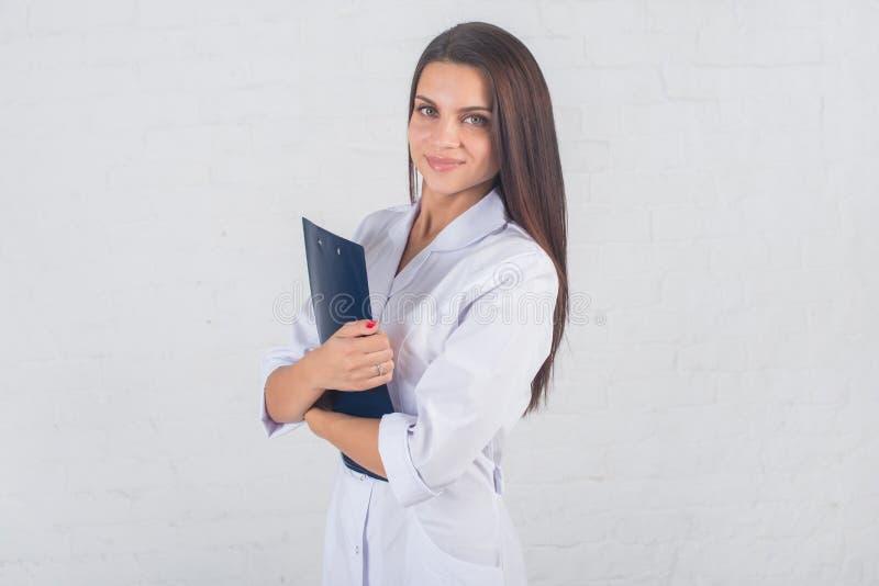 Retrato del doctor de la mujer en el pasillo del hospital, sosteniendo la tableta, mirando la cámara, sonriendo foto de archivo libre de regalías