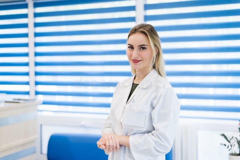 Retrato del doctor de la mujer joven con la capa blanca que se coloca en hospital foto de archivo libre de regalías