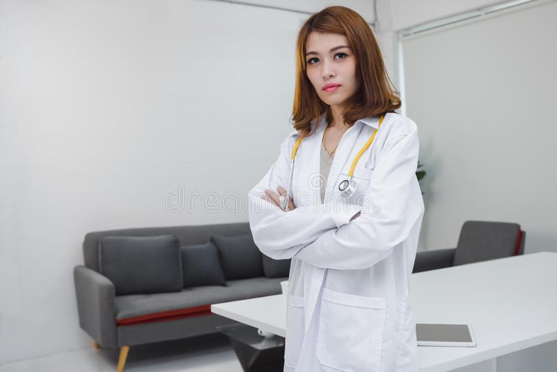 Retrato del doctor de sexo femenino asi?tico joven de la medicina que se coloca en el lugar de trabajo de la oficina del hospital imagenes de archivo