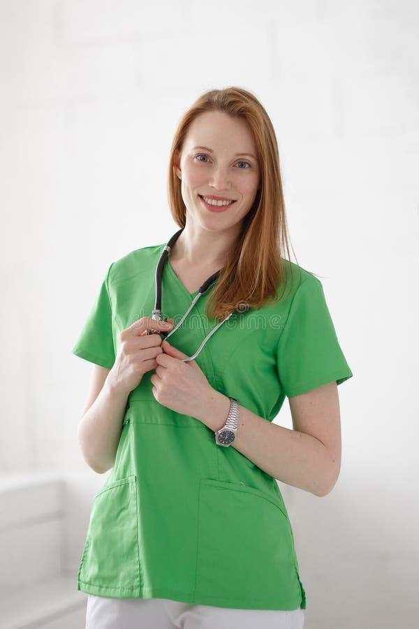 Retrato del doctor de sexo femenino confiado amistoso, sonriente, profesional de la atención sanitaria con la capa verde del labo imagen de archivo