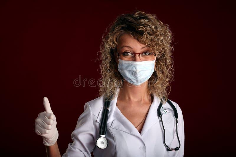 Retrato del doctor de sexo femenino joven con los pulgares para arriba foto de archivo libre de regalías