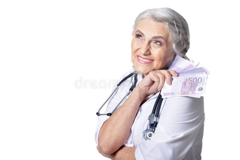 Retrato del doctor de sexo femenino maduro con el dinero, presentando contra blanco foto de archivo libre de regalías
