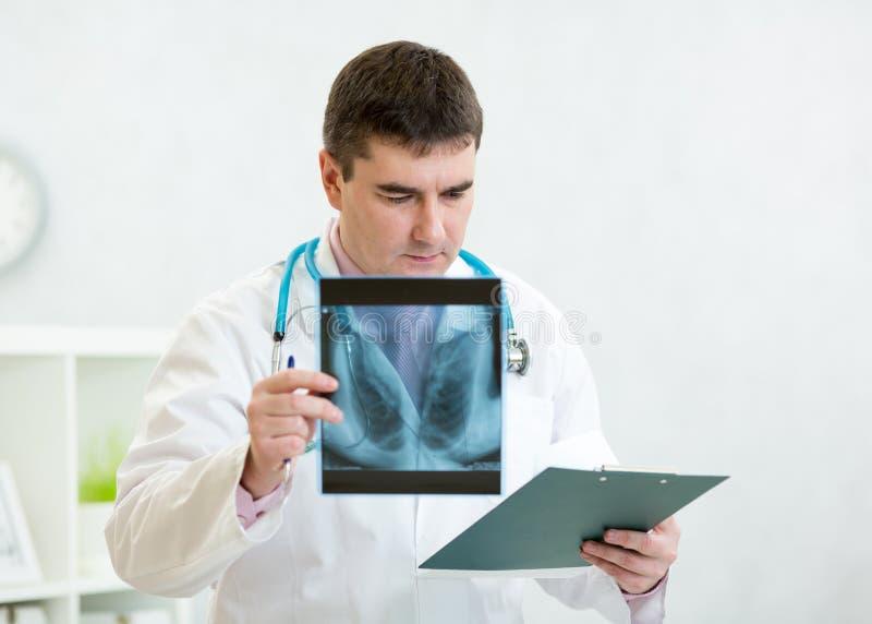 Retrato del doctor de sexo masculino con el tablero en la oficina foto de archivo