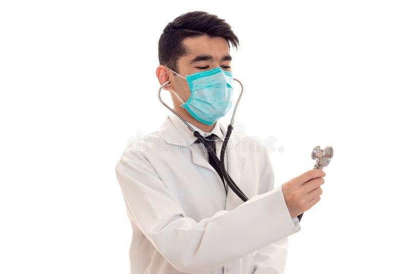 Retrato del doctor de sexo masculino moreno bastante joven en el uniforme y la máscara con la presentación del estetoscopio aisla fotos de archivo libres de regalías