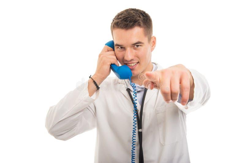 Retrato del doctor hermoso que detiene al receptor de teléfono que señala la cámara foto de archivo libre de regalías
