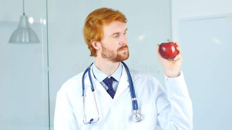 Retrato del doctor Holding y mirada de Apple rojo foto de archivo