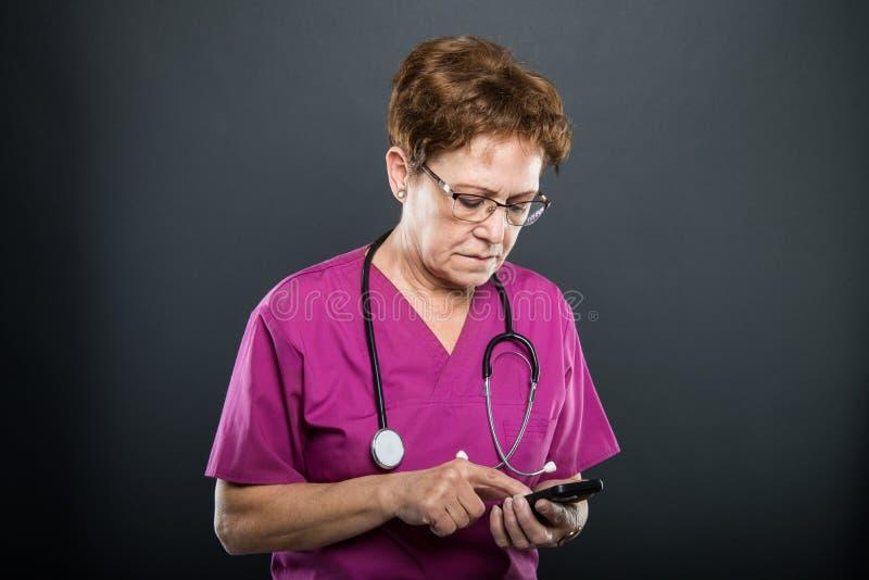 Retrato del doctor mayor de la señora que hojea en smartphone imagen de archivo
