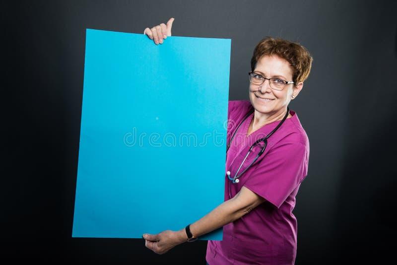 Retrato del doctor mayor de la señora que muestra al tablero azul grande foto de archivo