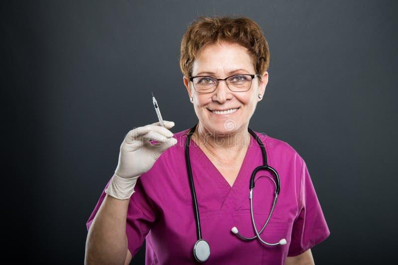 Retrato del doctor mayor de la señora que sostiene la jeringuilla fotografía de archivo